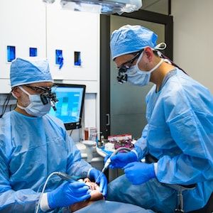Our team working on a patient and performing periodontal surgery using bone morphogenetic protein
