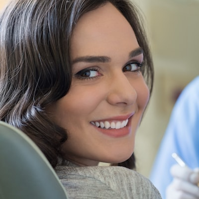 Patient smiling after her scaling to prevent the spread of periodontal disease