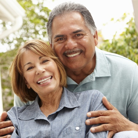 Implant dentures San Francisco - Couple hugging and smiling with their bar attachment dentures