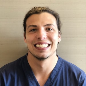 Our team member, Sebastian, wearing scrubs and smiling