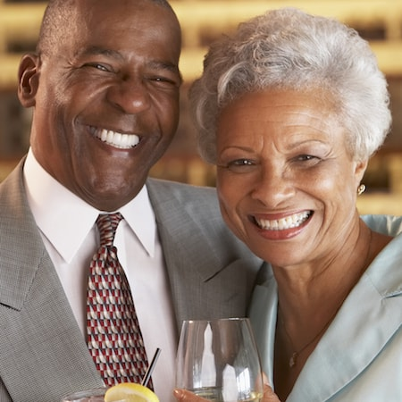 Older couple smiling with a drink after having received screw retained dentures in San Francisco